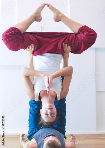 Foto op Aluminium School de yoga Young athletic couple practicing acroyoga. Balancing in pair