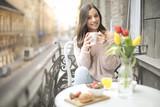 Sweet girl having a delicious breakfast on the balcony - 199175527