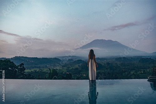 beautiful girl staying near swimming pool with fantastic volcano Agung view