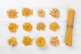 Various pasta on white wooden table - 199182311