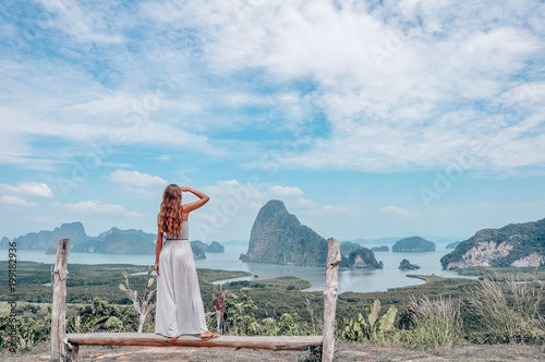 Foto Murales beautiful girl  staying on the top of hill with fantastic panoramic view on beautiful Thai bay