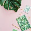 Monstera leaf, notebook, pen, scissors made with tropical palm style on pink background. Flat lay, top view minimal  concept.