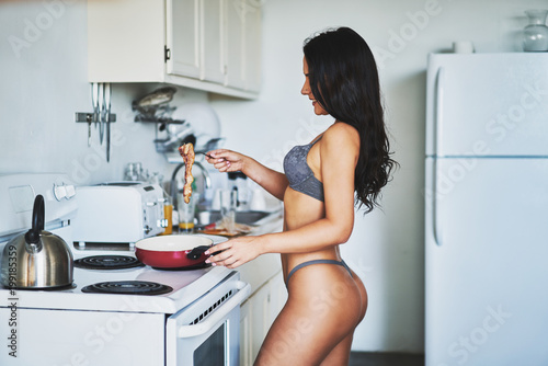 sexy brunette women in lingerie cooking bacon in kitchen