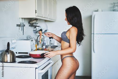 obraz lub plakat sexy brunette women in lingerie cooking bacon in kitchen