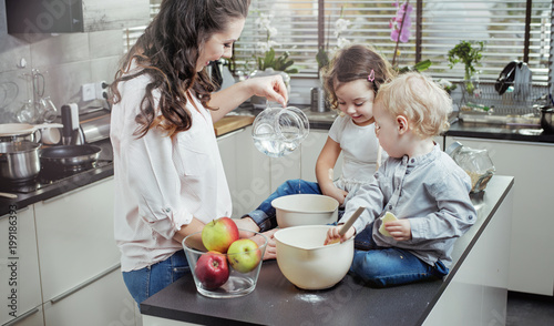 Fotobehang Artist KB Cheerful mother teaching her children how to bake a cake