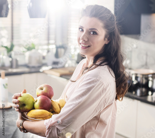 Fotobehang Artist KB Cheerful woman holding a bowl full of fruit
