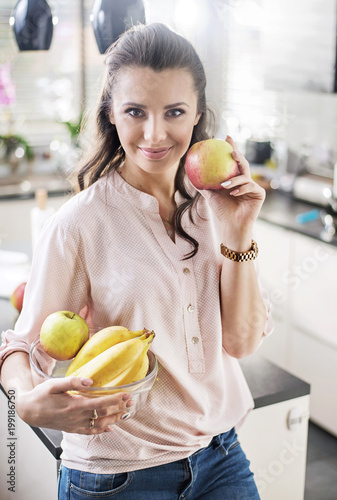 Fotobehang Artist KB Brunette woman holding a fruit bowl