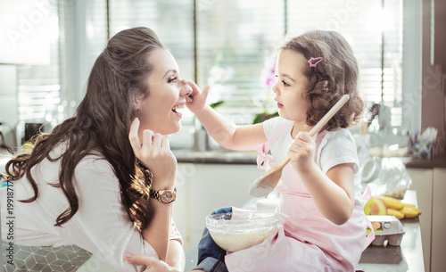 Canvas Konrad B. Pretty mother and her daughter preparing a cake