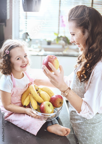 Foto Murales Cheerful family in a kitchen - fruit diet theme