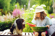summer happy child girl eating watermelon outdoor on vacation, and sharing it with her dog