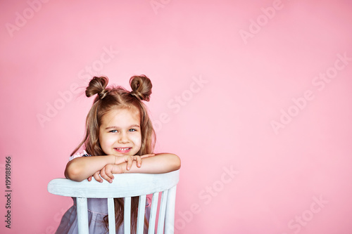 cute little girl sits on a white chair smiling and looks at the camera on a pink background with copy space