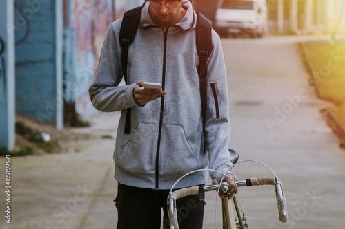 young in town with mobile phone and bike