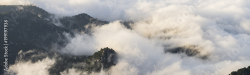 Foto op Plexiglas Panoramafoto s Aerial view on mountaintops covered with clouds during sunrise
