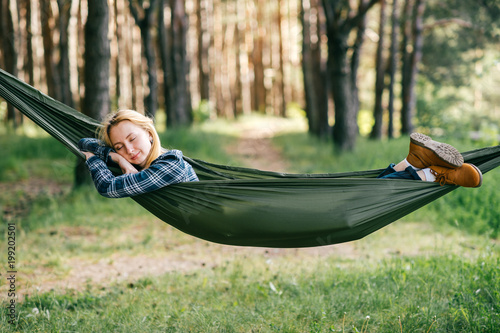 Outdoor lifestyle portrait of young beautiful blonde girl sleeping in hammock in forest. Cute woman dreaming at nature in summer. Tired female resting in camping trip after hard walk. Travel equipment