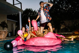 Friends partying in a pool in evening