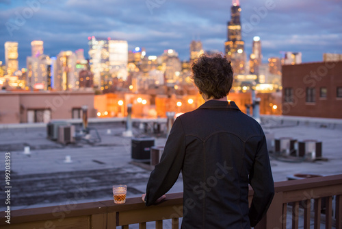 Poster Chicago Attractive, forty something man, with long, curly brunette hair, on a rooftop, in the city, with cityscape in the distance. Dusk and sunset lights. Staring into the distance. Contemplating the future.