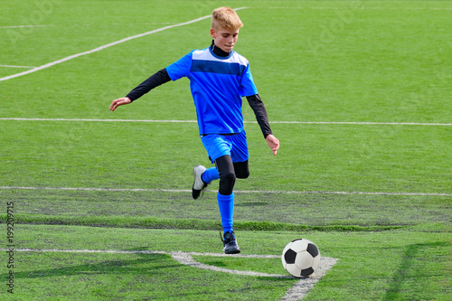 Teenage blonde Caucasian soccer (football) player in blue sport uniform is going to kick ball in corner kick during game on grass field on sunny day