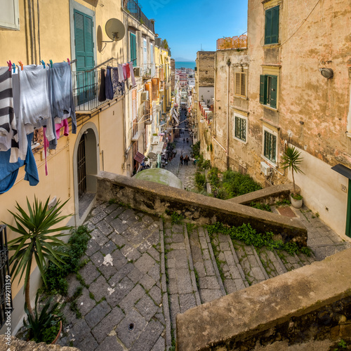 Poster Smal steegje Una tipica strada antica di Napoli, con i panni appesi ai balconi, le scale e la strada che porta verso il mare