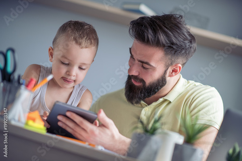 Young father playing with his son at home office