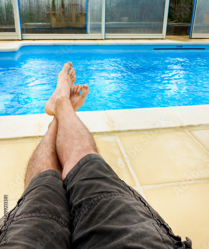 Man sunbathing near swimming pool, Brittany, France, Europe