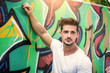 Attractive muscle man leaning on colorful graffiti wall, wearing white t-shirt
