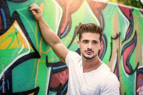 Atrakcyjny mężczyzna mięśni, opierając się na kolorowe graffiti ściany, ubrany w biały t-shirt