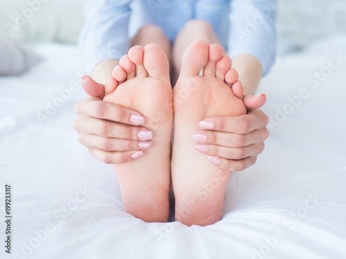 Young woman massaging her foot on the bed., Healthcare concept.