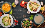A set of healthy food in plates. Caesar salad, seafood, pumpkin soup and mushrooms. Top view. On a wooden background. Copy space. - 199243527