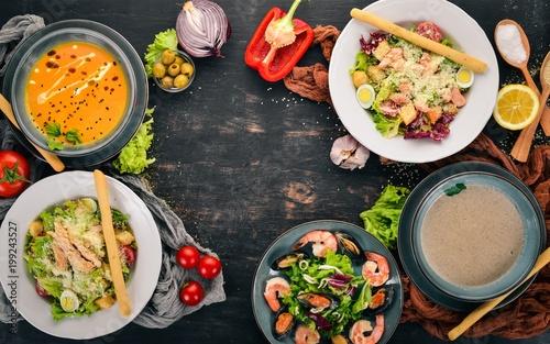 Zestaw zdrowej żywności w płytkach. Sałatka Cezar, owoce morza, zupa dyniowa i grzyby. Widok z góry. Na drewnianym tle. Skopiuj miejsce.