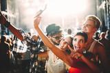 Happy friends taking selfie at music festival - 199246121