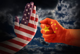 Trade conflict, USA flag on a stop hand and China flag on a fist against a dramatic cloudy sky - 199262799