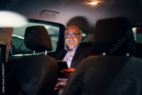Mature professional happy successful businessman is being driven in the back seat of the car while using a tablet.