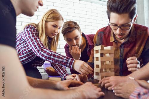 Wesoła grupa przyjaciół gra w gry planszowe w pokoju.