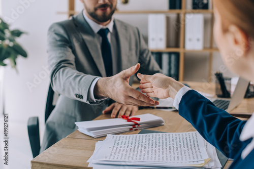 partial view of lawyers shaking hands on meeting in office