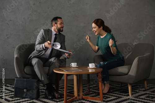 side view of happy woman sitting at table while having meeting with lawyer