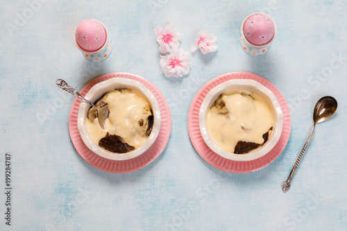 Traditional Finnish Easter pudding, Mammi, rye pudding with Vanilla cream in Heart shaped Ceramic dish and pastel color ceramic spoon on blue background with Easter decorations, top view