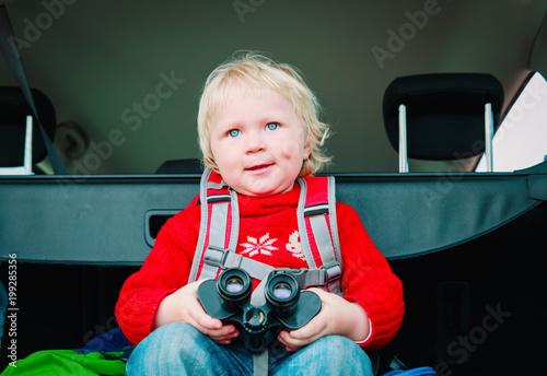 little baby looking through binoculars travel by car