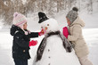 On a winter day, on the mountains with snow, a family plays with a snowman. Concept of: winter holidays, family, christmas, mountain