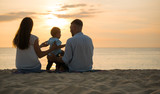 Parent family and baby sitting at sunset On the beach While relaxing on weekends with blur sea background in travel and holiday concept.