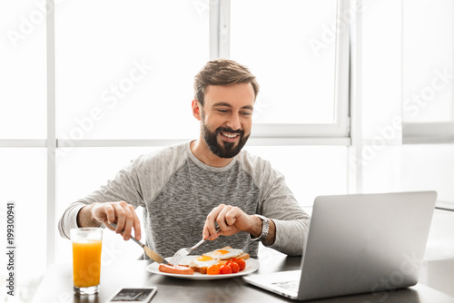 Unshaved satisfied man 30s wearing casual clothing eating fried eggs for breakfast, and looking at notebook - 199300941