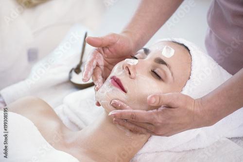 Masażysta robi kremowej masce na twarzy piękna młoda kobieta relaksuje w zdroju salonie.