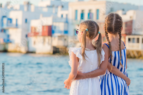 Adorable little girls on vacation on Mykonos island, Greece.