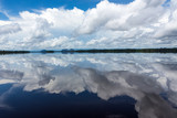 Beautiful reflection of blue sky and clouds in the waters of the Negro River with rainforest and hills in the background.