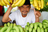 Man selling yellow bananas on local market in thailand
