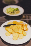 potatoes and zucchinis being sliced on a plate to prepare a meal - 199324594