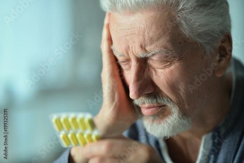 Elderly ill man with pills in hand - 199325391