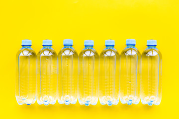 Plastic bottles with pure water on yellow background top view