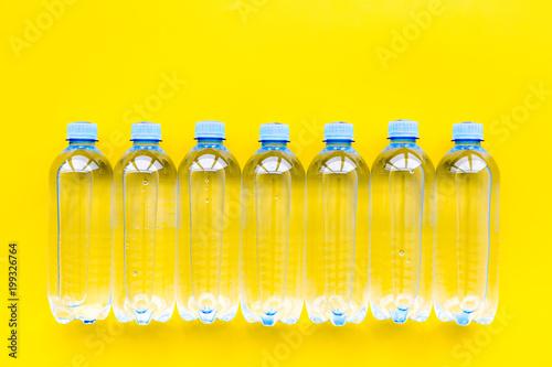 Plastikowe butelki z czystą wodą na żółtego tła odgórnym widoku