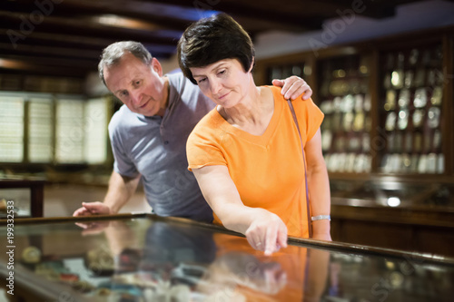 Senior couple is looking at the exposition under glass