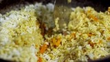 Close up shot of rice pilaf with meat and carrots seasoned with cumin seeds, cook stirring it with slotted spoon - 199335900